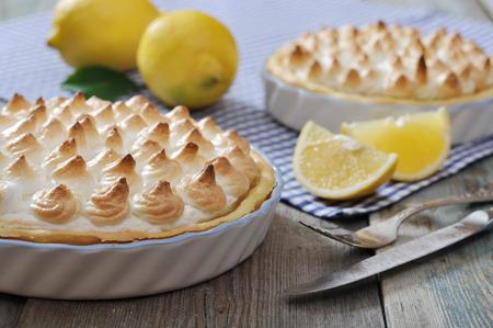 pie de limon: Tarta de merengue limón con limones frescos en el fondo a cuadros Foto de archivo