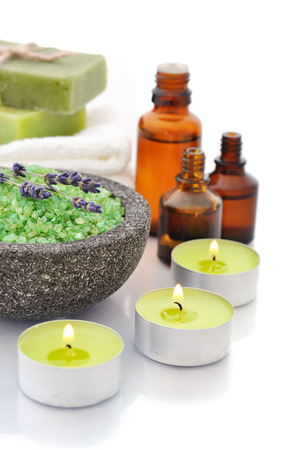 Sea salt in stone bowl with candles and herbal soap isolated on a white background with reflection photo
