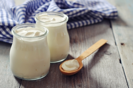 Greek yogurt in a glass jars with spoons on wooden background Фото со стока