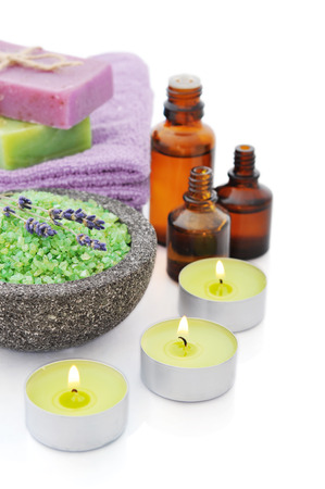 aromatherapy oil: Sea salt in stone bowl with candles and herbal soap isolated on a white background with reflection