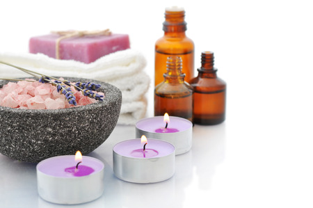 Sea salt in stone bowl with candles and herbal soap isolated on a white background with reflection