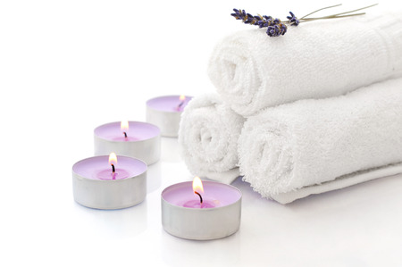 White spa towels pile with lavender and candles on white background