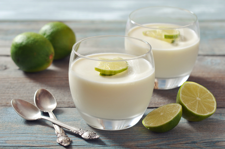 panna cotta: Italian dessert panna cotta with fresh lime in glass on wooden background