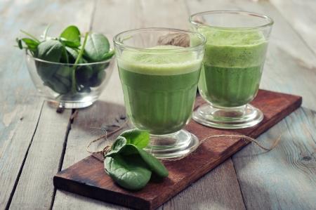 jugo verde: Apple y batido de espinacas en vidrio sobre un fondo de madera