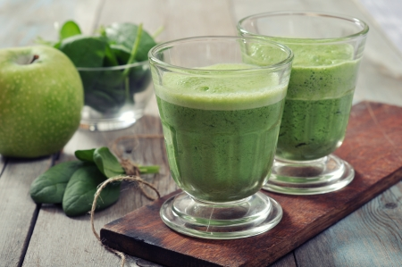 Apple and spinach smoothie in glass on a wooden background photo