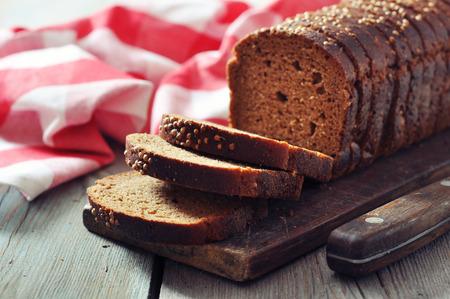 black bread: Sliced rye bread on cutting board closeup Stock Photo