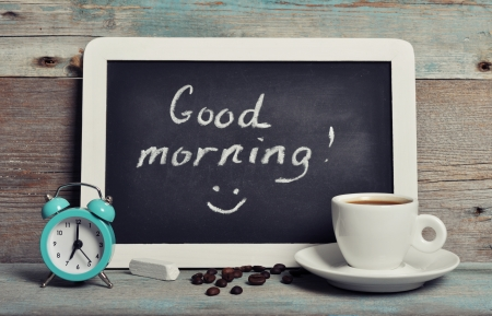 good morning: Cup of coffee with blackboard and alarm clock on vintage wooden background