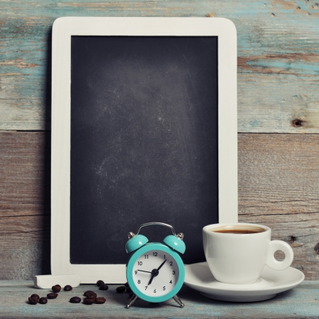 Cup of coffee with blackboard and alarm clock on vintage wooden background  photo