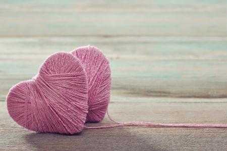 gomitoli di lana: Due bugne rosa a forma di cuore su sfondo vintage di legno