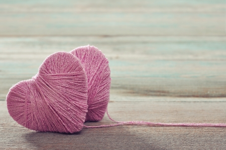Two pink clews in shape of heart on vintage wooden background Stok Fotoğraf