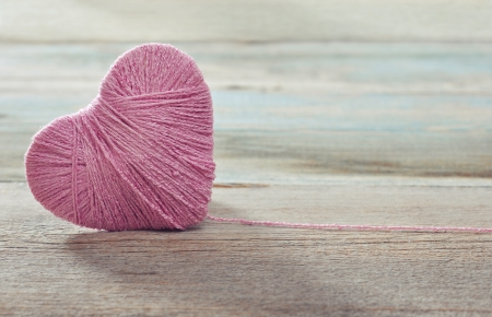 Pink clew in shape of heart on vintage wooden background photo