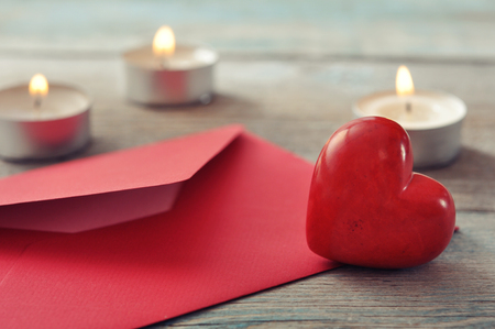 Red envelop with stone heart and candles on wooden background photo
