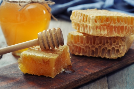 Honeycomb with honey dipper on vintage wooden background  photo
