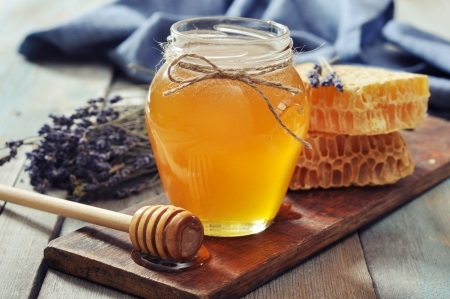 organic background: Honey in jar with honey dipper on vintage wooden background