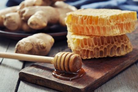 ginger health: Honeycomb with fresh ginger on vintage wooden background