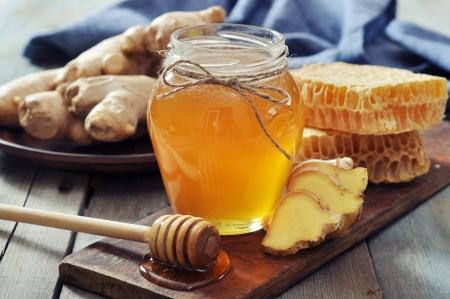 ginger health: Honey in jar with fresh ginger on vintage wooden background