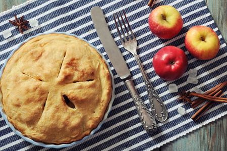 Homemade apple pie with fresh apples on wooden background