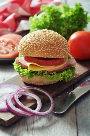 ham sandwich: Sandwich with ham, cheese,  tomato and lettuce on wooden cutting board closeup Stock Photo