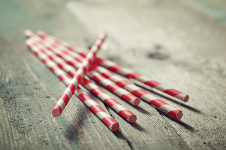 Striped straws for cocktails on wooden background