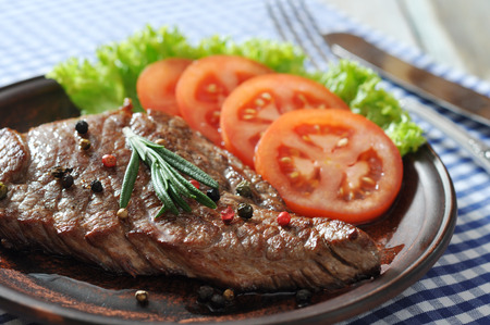rumpsteak: Grilled steak  on plate  with tomatoes, spices and rosemary closeup Stock Photo
