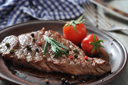 Grilled steak  on plate  with tomatoes, spices and rosemary closeup Stock Photo - 23949034