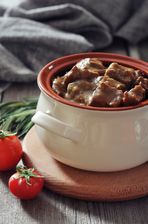 Goulash in a ceramic pot with tomatoes, spices and rosemary on a wooden background Stock Photo - 23949039