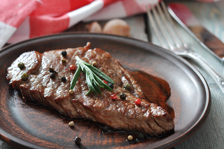 Grilled steak  on plate  with tomatoes, spices and rosemary closeup Stock Photo - 23949069