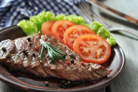 Grilled steak  on plate  with tomatoes, spices and rosemary closeup Stock Photo - 23949070