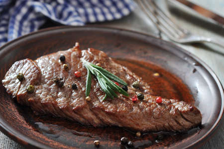 Grilled steak on plate with spices and rosemary closeup photo