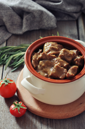 Goulash in a ceramic pot with tomatoes, spices and rosemary on a wooden background Stock Photo - 23949110