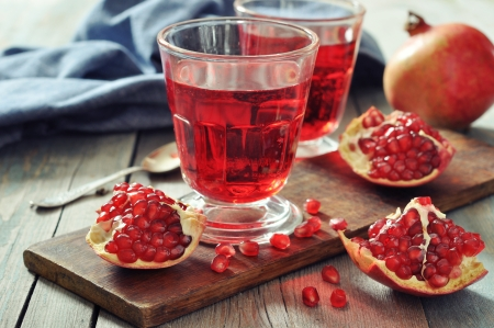 pomegranate juice: Ripe pomegranate fruit and glass of juice on wooden background Stock Photo