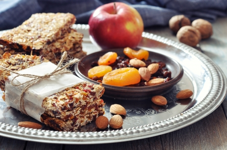 Granola bars on plate with nuts and dried fruits on wooden background photo