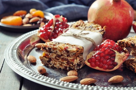 Granola bars on plate with nuts, pomegranate and dried fruits on wooden background photo