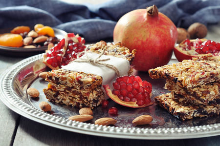 granola bar: Granola bars on plate with nuts, pomegranate and dried fruits on wooden background