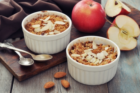 Apple crumble in ceramic molds with fresh apples on wooden background Stock Photo