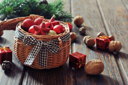 Christmas decorations in wicker basket and fir tree on wooden background photo
