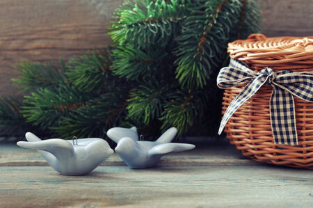 Christmas decoration in shape of birds, wicker basket and fir tree on wooden  photo