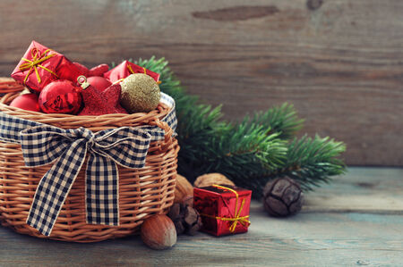 Christmas decorations in wicker basket with fir tree on wooden  photo