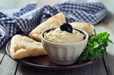 pita bread: Bowl of fresh hummus  with olive and bread slices on wooden  Stock Photo