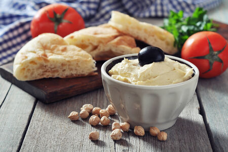 Bowl of fresh hummus  with olive and bread slices on wooden  Stock Photo - 24148585