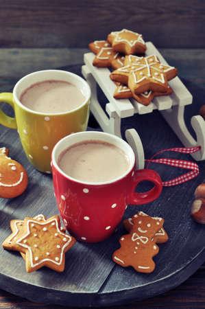 cioccolato natale: Tazze di cioccolata calda con slitta giocattoli e zenzero biscotti su una tavola di legno