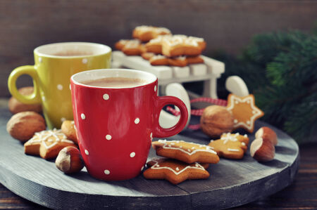 cups of hot chocolate with toy sled and ginger biscuits on a wooden  Stock Photo