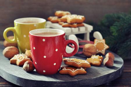 cioccolato natale: tazze di cioccolata calda con la slitta giocattolo e biscotti allo zenzero su una tavola di legno Archivio Fotografico