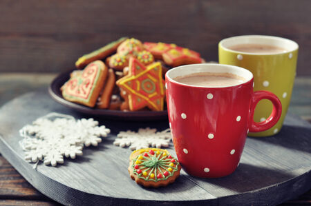 Two cups of hot chocolate and ginger biscuits on a wooden  photo