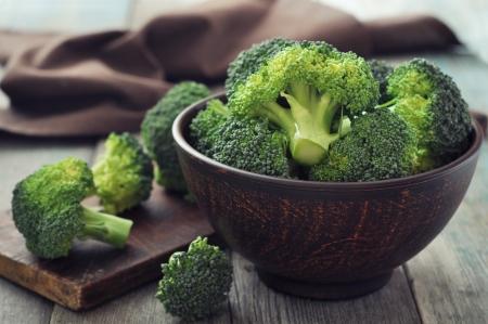 brocoli: Manojo de brócoli verde fresca en tazón de café sobre fondo de madera