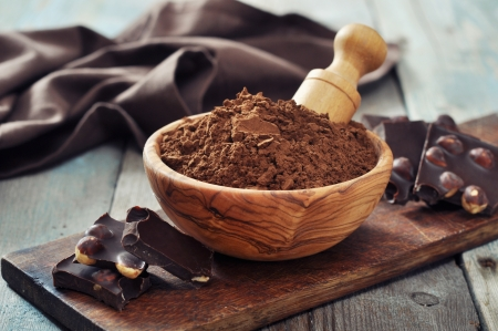 Carob powder in bowl with chocolate pieces on wooden tray