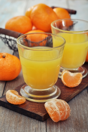 Tangerine juice in glass with fresh fruits on wooden background  photo