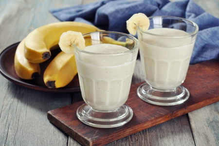 licuado de platano: Batido de plátano en vaso con frutas frescas en el piso de madera Foto de archivo