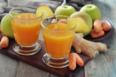 Apple and carrot juice in glass with ginger,  fresh vegetables and fruits on wooden tray
