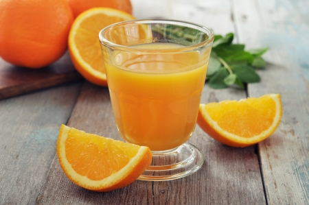 orange slice: Sinaasappelsap in glas met munt en vers fruit op houten vloer